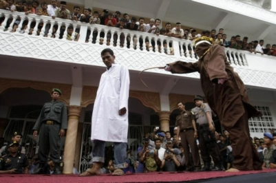 People watch as an Acehnese man, one of eight who was found guilty of gambling by a Sharia court, receives a public flogging outside a mosque in the provincial capital of Banda Aceh September 19, 2014. Aceh is Indonesia's only province to have implemented Sharia, or Islamic laws. REUTERS/Junaidi Hanafiah (INDONESIA - Tags: RELIGION CRIME LAW TPX IMAGES OF THE DAY) - RTR46Y7U